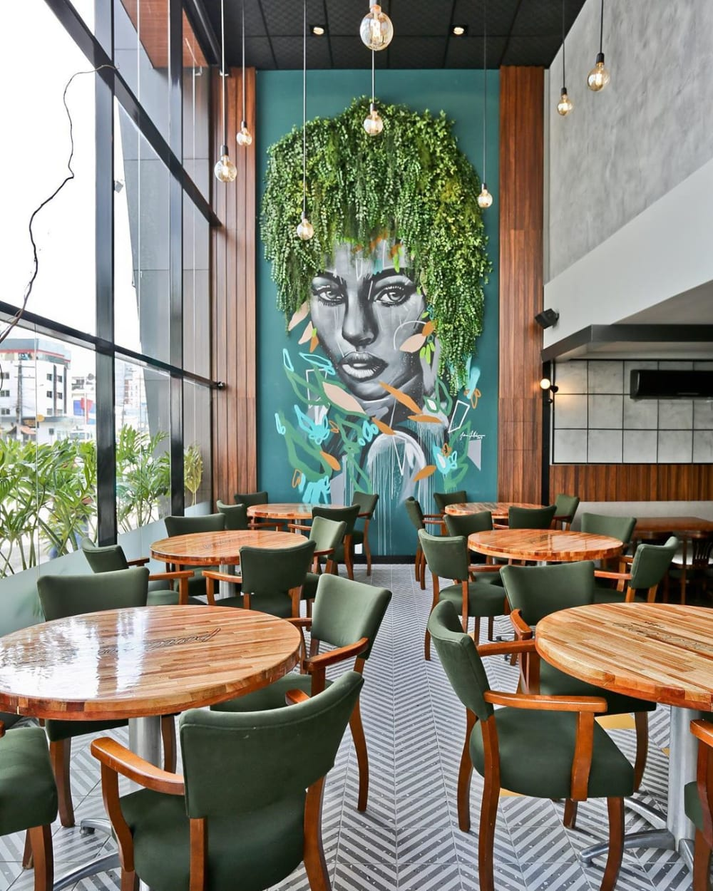 "Restaurant with draping plants used as the hair of a female face drawn on the wall.<span class=""sr-only""> (opened in a new window/tab)</span>"