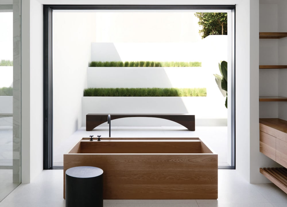"Bathroom overlooking a patio dressed up with greenery arranged in line with the minimalist style of the interior.<span class=""sr-only""> (opened in a new window/tab)</span>"