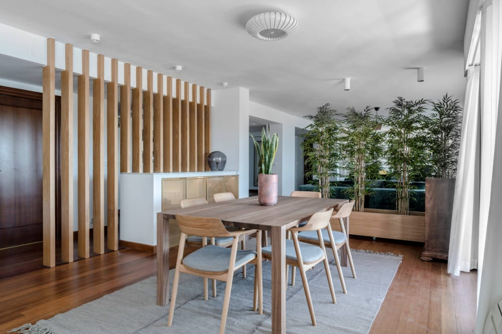"""Tall plants visually dividing a dining room area.<span class=""""sr-only""""> (opened in a new window/tab)</span>"""
