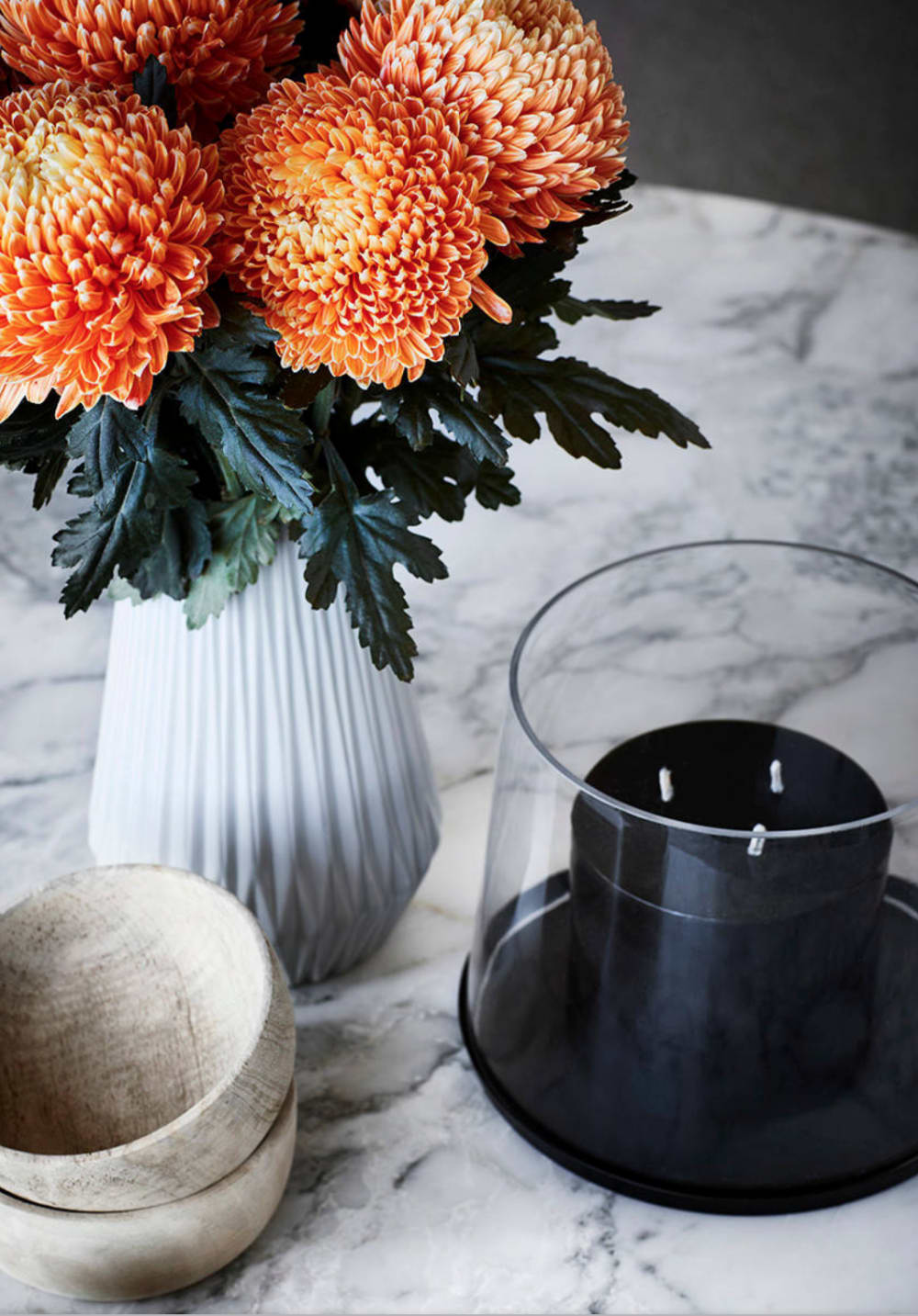 "Close-up of a styling with a black candle, wooden bowl and bold orange flowers.<span class=""sr-only""> (opened in a new window/tab)</span>"