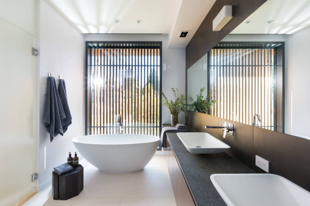 "Natural bathroom design filled with natural light. A vertical wall panelling adds privacy<span class=""sr-only""> (opened in a new window/tab)</span>"