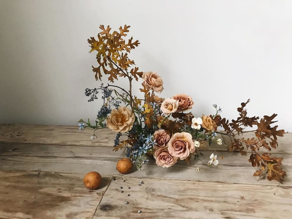 """An arrangement of brown leaves and roses.<span class=""""sr-only""""> (opened in a new window/tab)</span>"""