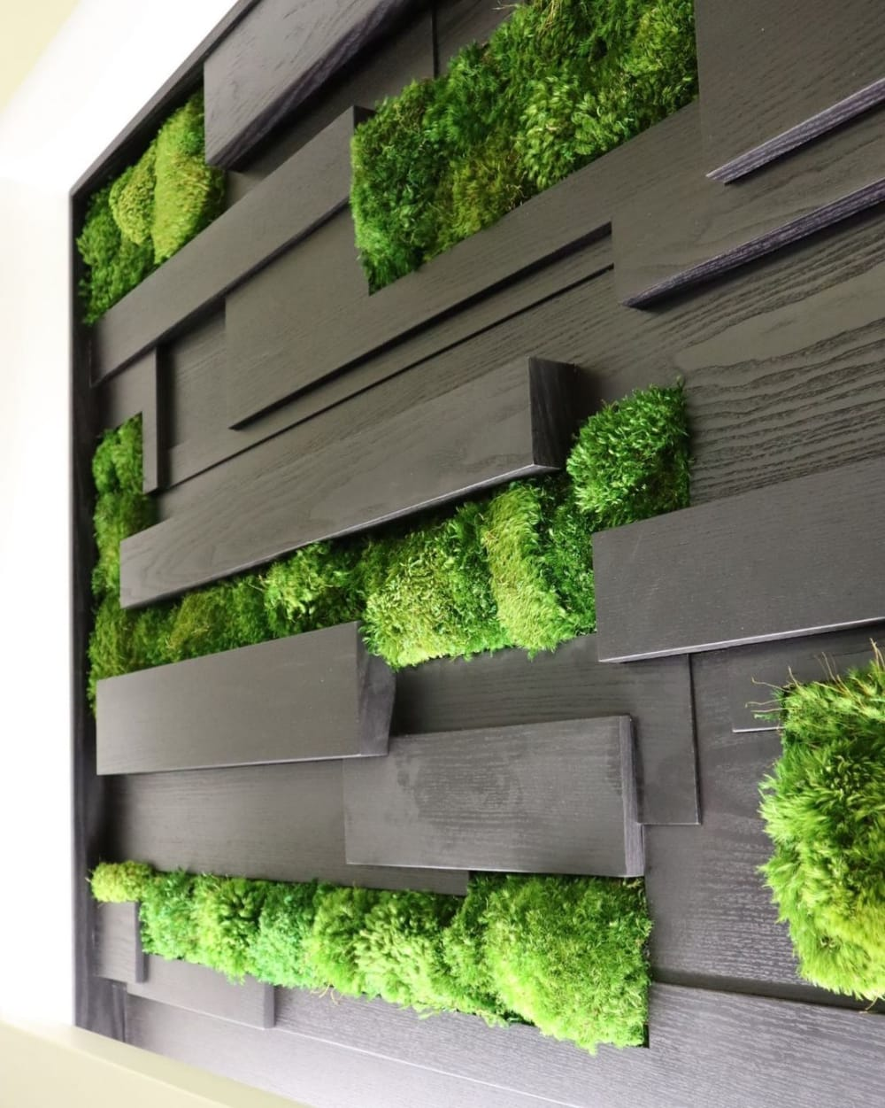 """Close-up of a black wooden wall with moss insets.<span class=""""sr-only""""> (opened in a new window/tab)</span>"""