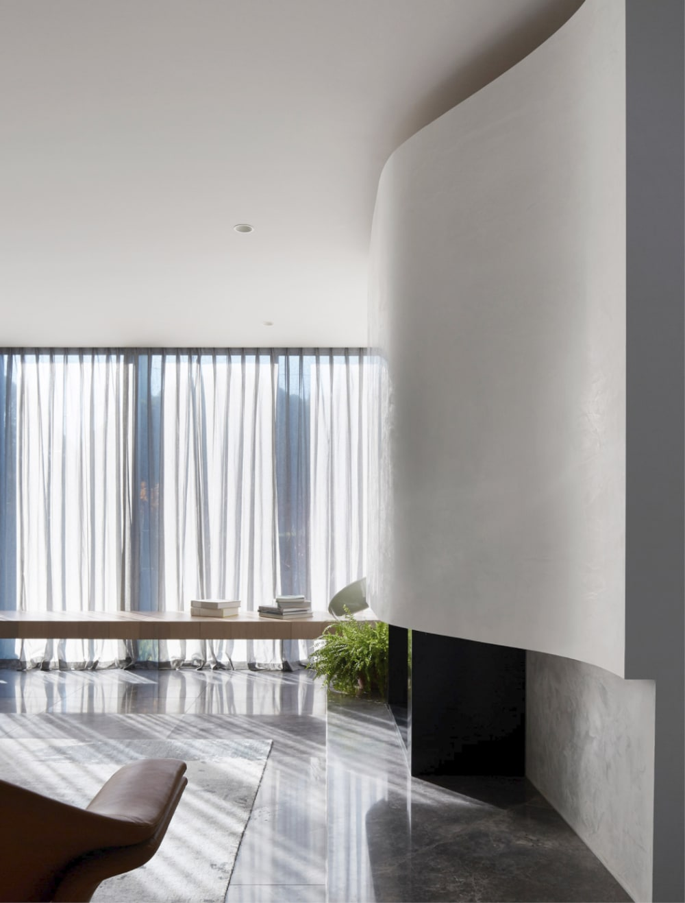 """Biophilic living room flooded with natural light, with a curved wall giving a sense of calm.<span class=""""sr-only""""> (opened in a new window/tab)</span>"""