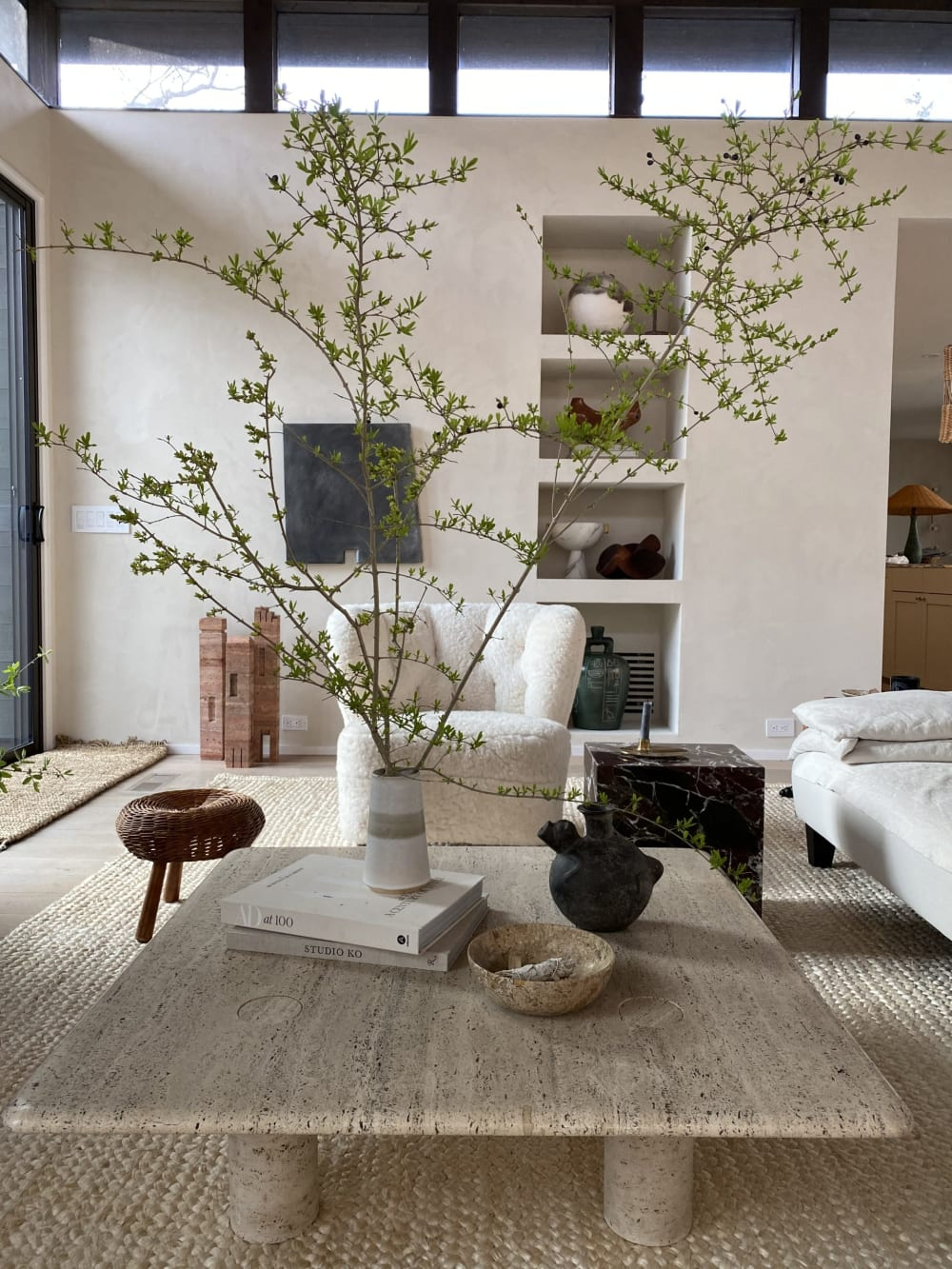 """Biophilic living room with plenty of soft juxtaposed textures and an oversized branch decorating the space.<span class=""""sr-only""""> (opened in a new window/tab)</span>"""