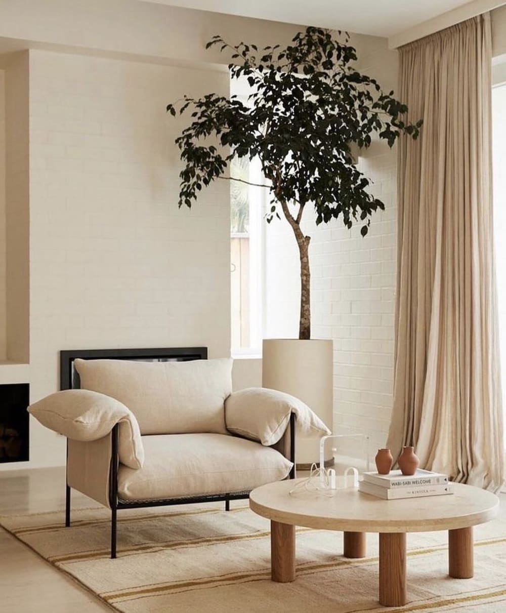 """Cozy corner in a living room, created next to a window with a soft armchair and a tall tree.<span class=""""sr-only""""> (opened in a new window/tab)</span>"""