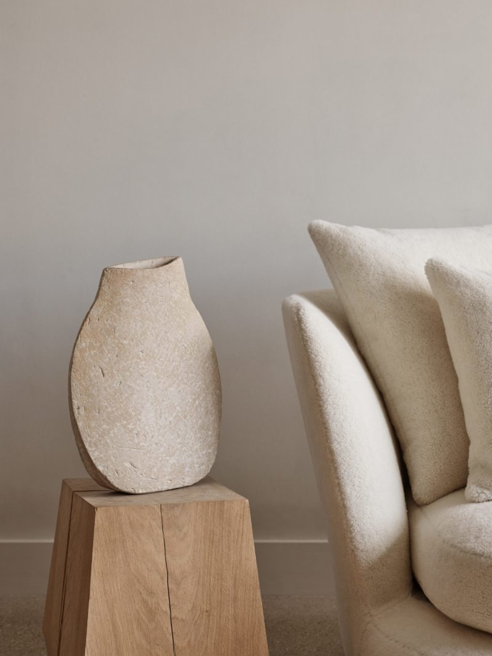 """A tonal juxtaposition of textures: rough stone vase over a wooden stool next to a soft armchair.<span class=""""sr-only""""> (opened in a new window/tab)</span>"""