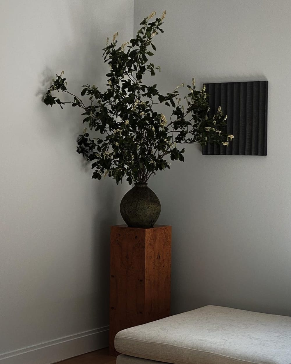 """Oversized branch styled over a wooden stool in the corner of a room.<span class=""""sr-only""""> (opened in a new window/tab)</span>"""