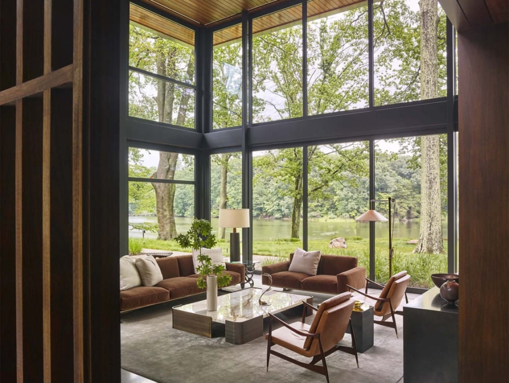 """Earthy living room with a stunning view of a lakeside.<span class=""""sr-only""""> (opened in a new window/tab)</span>"""