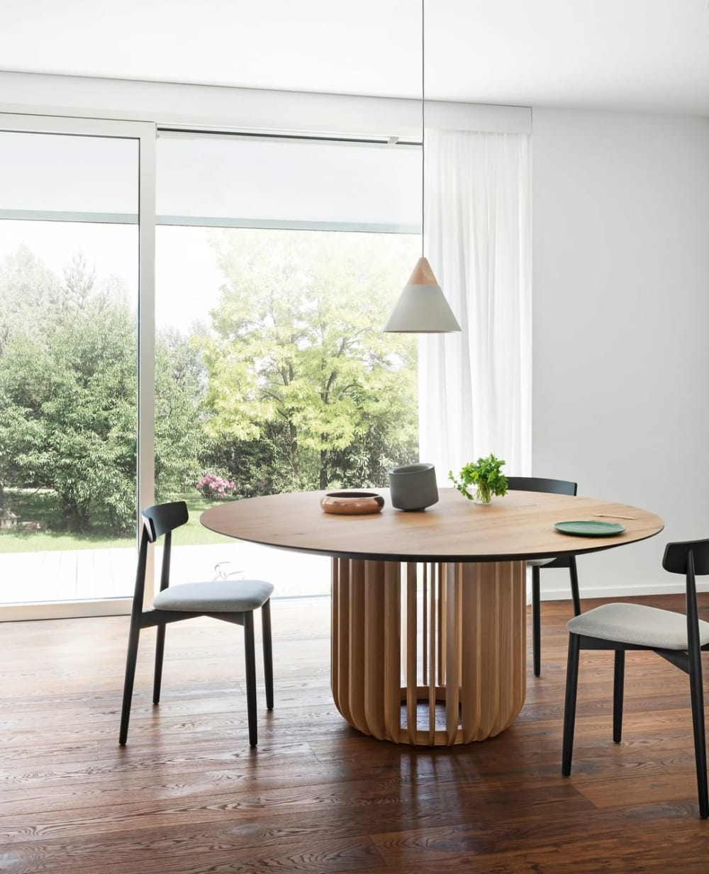 """Contemporary dining room with a big window looking into a garden.<span class=""""sr-only""""> (opened in a new window/tab)</span>"""