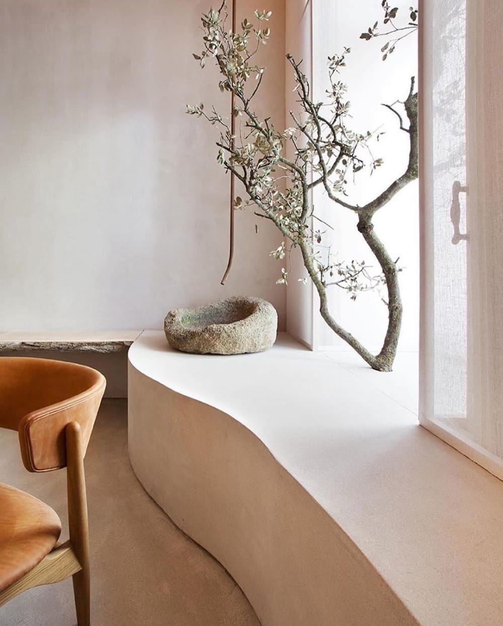 """Detail of a contemporary living room with a simple branch used as decor.<span class=""""sr-only""""> (opened in a new window/tab)</span>"""
