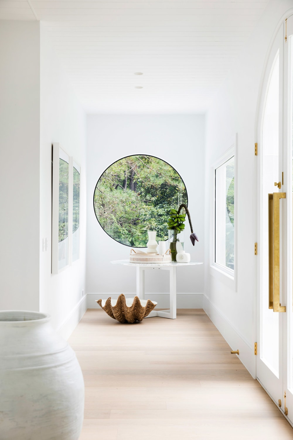 """White airy corridor with a round window looking into greenery on the back wall.<span class=""""sr-only""""> (opened in a new window/tab)</span>"""