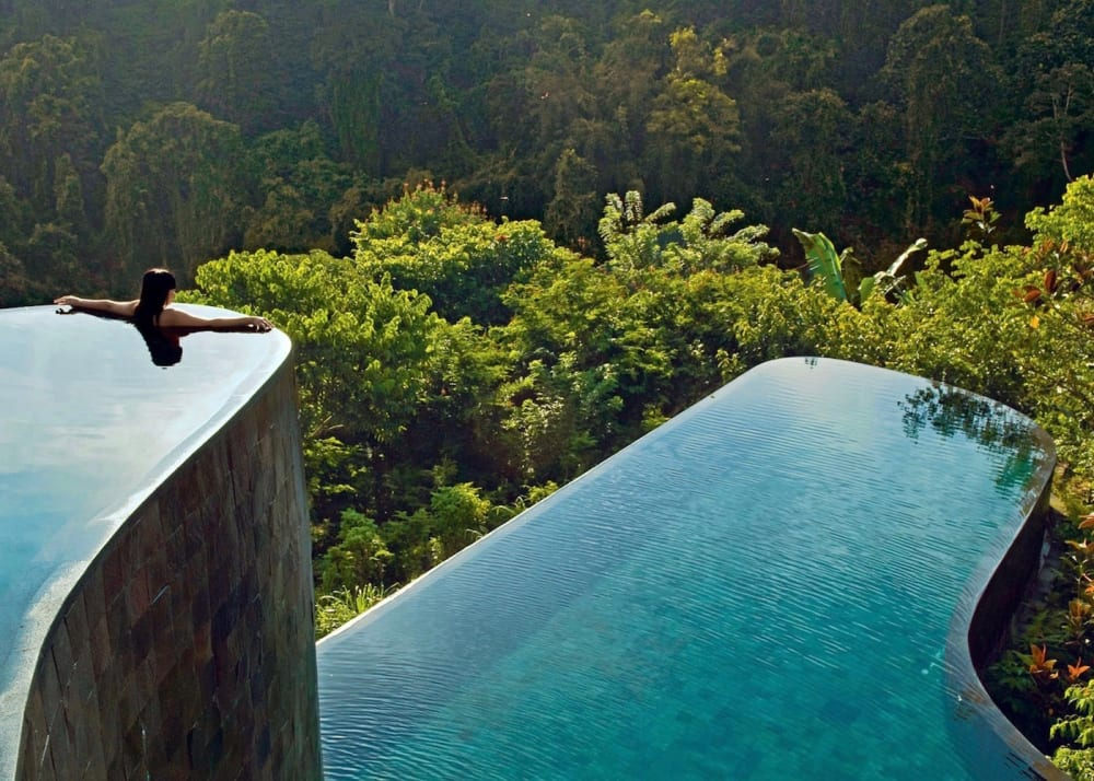 "A terraced infinity pool that seems to go right into the forest with a woman on the edge.<span class=""sr-only""> (opened in a new window/tab)</span>"