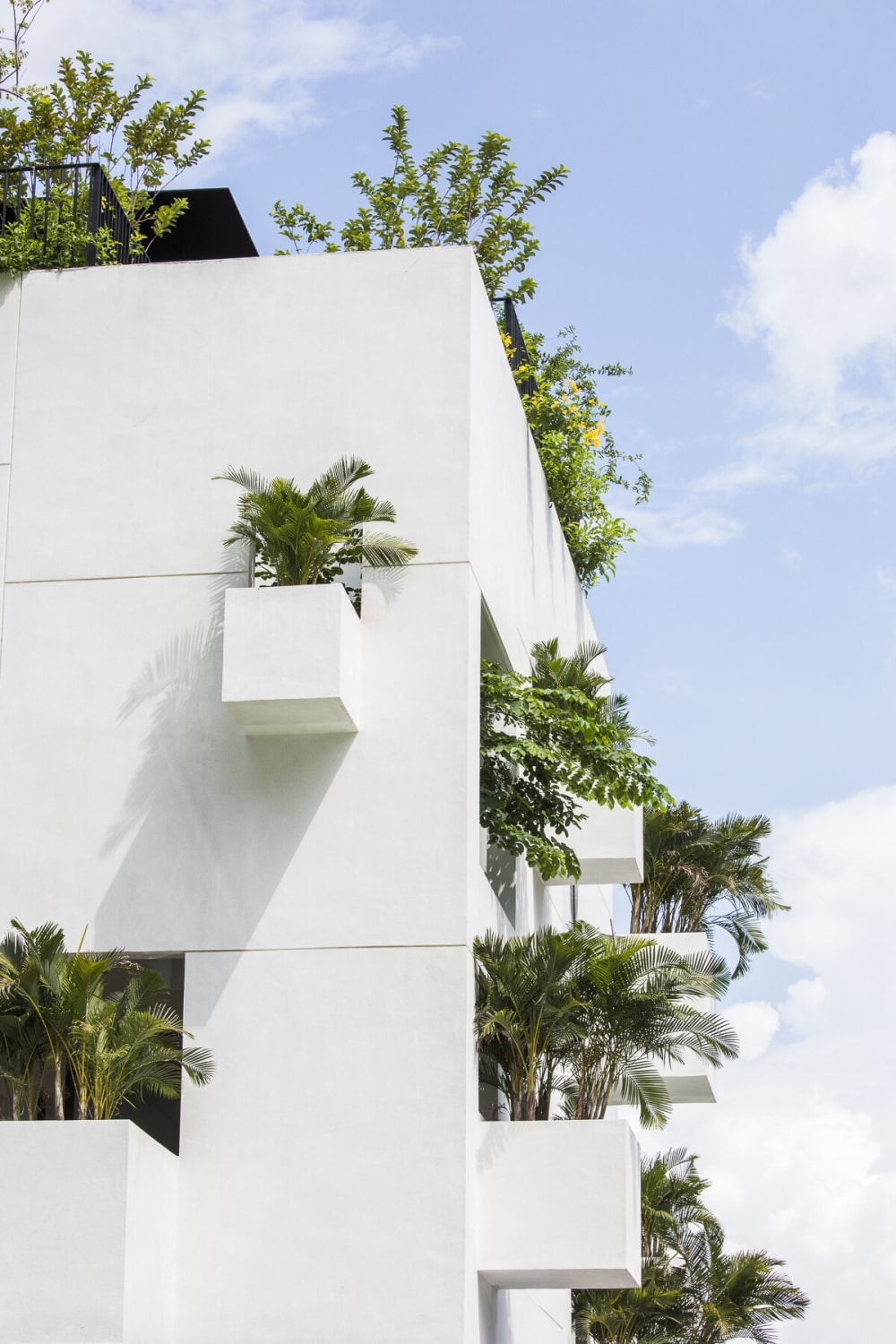"""Boxy building with protruding balconies filled with plants.<span class=""""sr-only""""> (opened in a new window/tab)</span>"""
