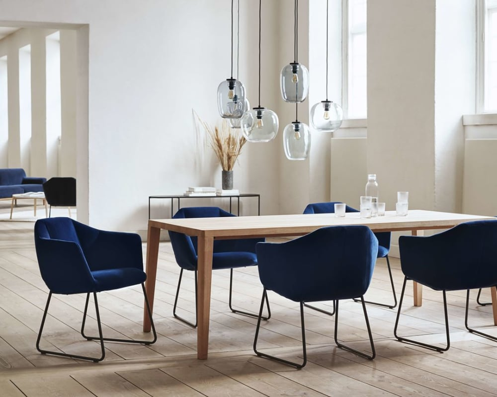 "Dining room flooded with natural light, with light wood floors and walls and blue accent dining chairs.<span class=""sr-only""> (opened in a new window/tab)</span>"