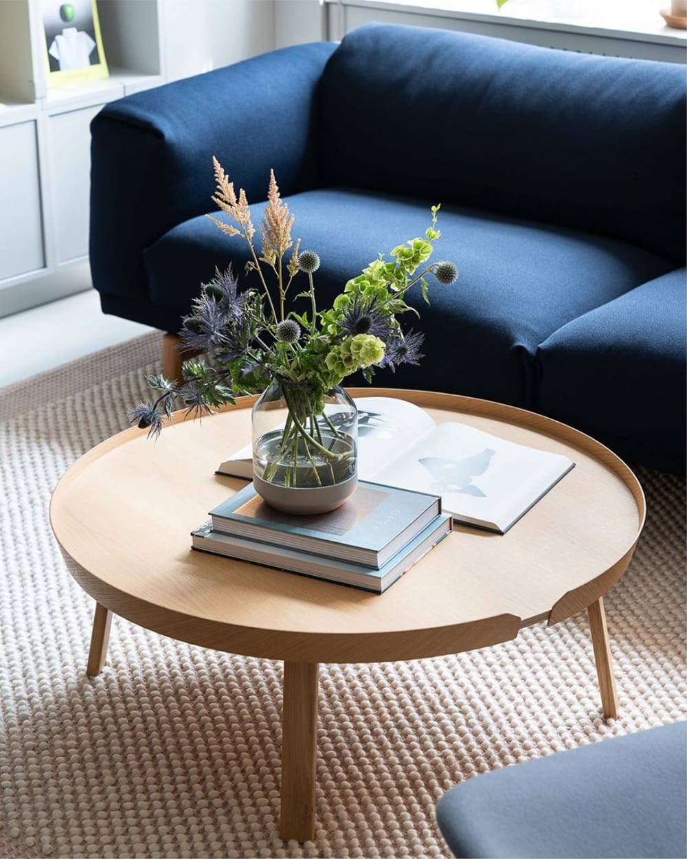 "Close-up of a blue sofa and a bunch of flowers over a light wood coffee table.<span class=""sr-only""> (opened in a new window/tab)</span>"