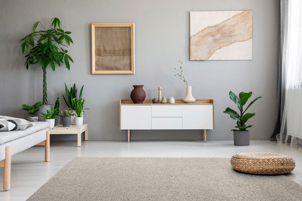"""Living room decorated with earthy tones, plenty of plants and a beige modular rug on the floor.<span class=""""sr-only""""> (opened in a new window/tab)</span>"""