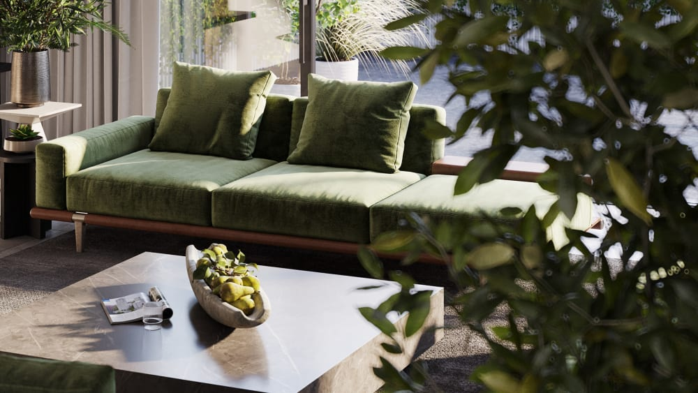 """Close-up shot of a sofa in a room full of greenery that overlooks a light patio.<span class=""""sr-only""""> (opened in a new window/tab)</span>"""