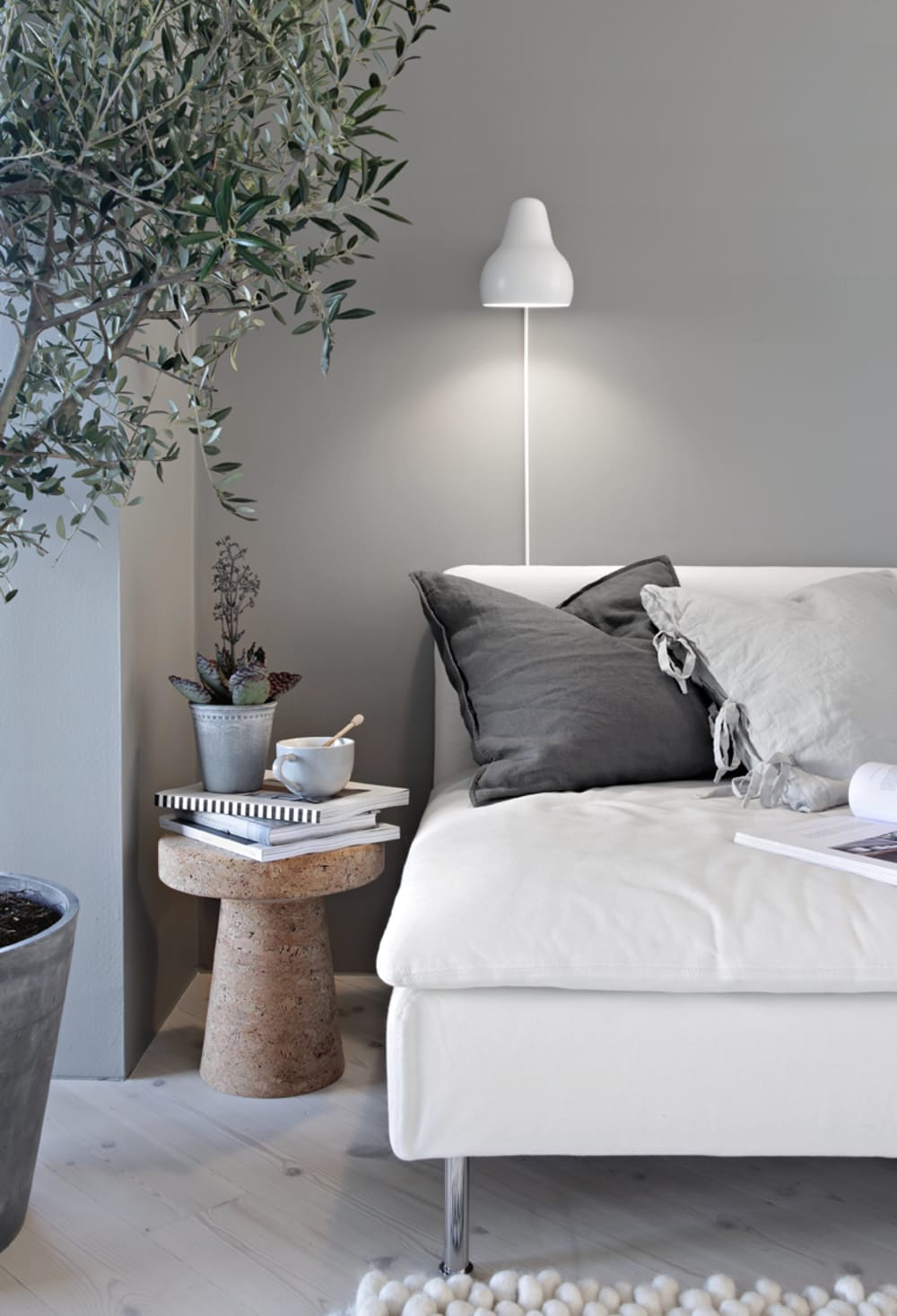 """Sofa with soft cushions, a tea and few plants.<span class=""""sr-only""""> (opened in a new window/tab)</span>"""