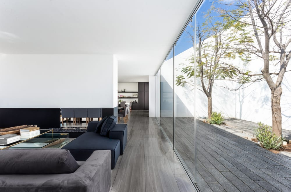 """Big indoor-outdoor living room with fully glazed wall looking into trees.<span class=""""sr-only""""> (opened in a new window/tab)</span>"""