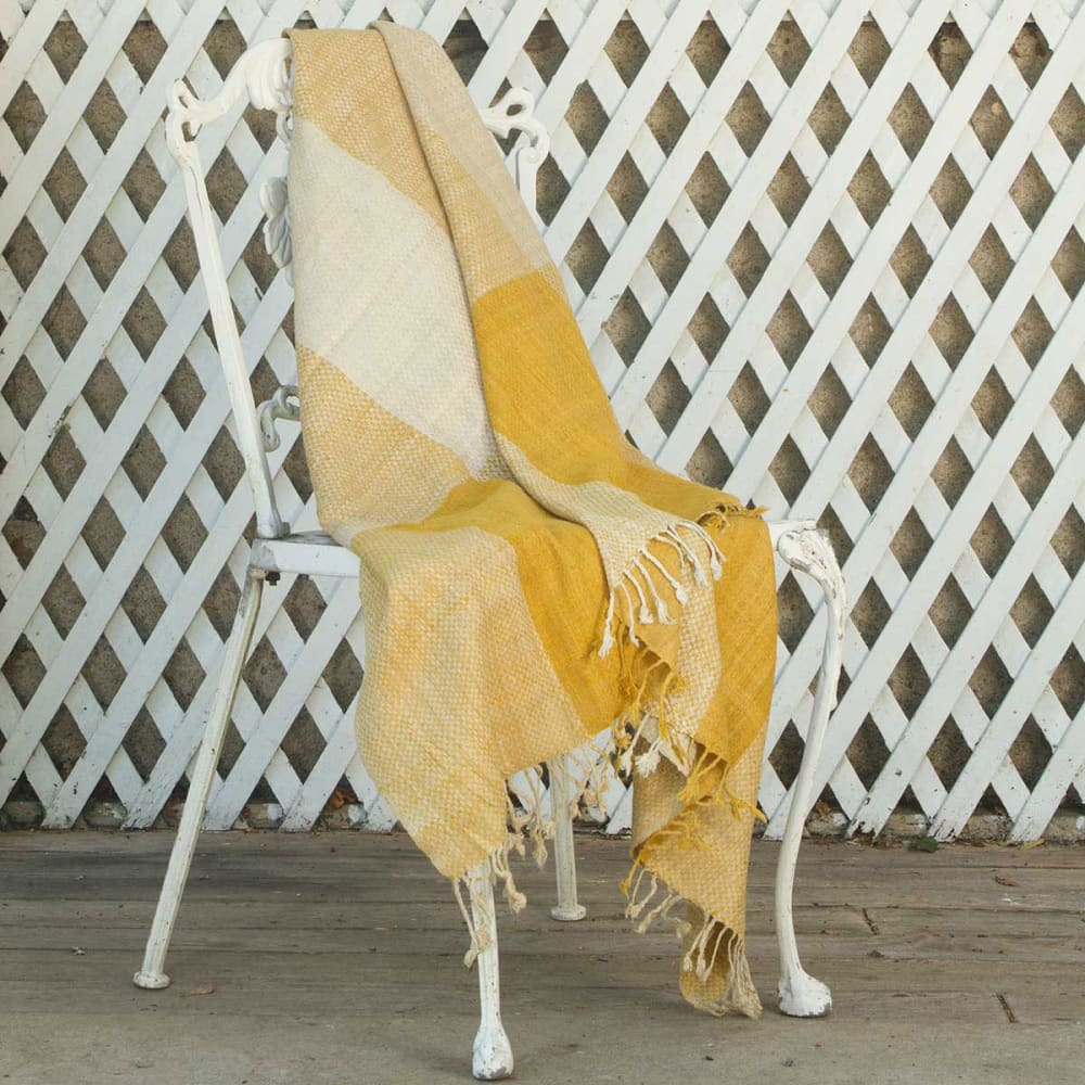 """Blanket laying on a white metal chair.<span class=""""sr-only""""> (opened in a new window/tab)</span>"""