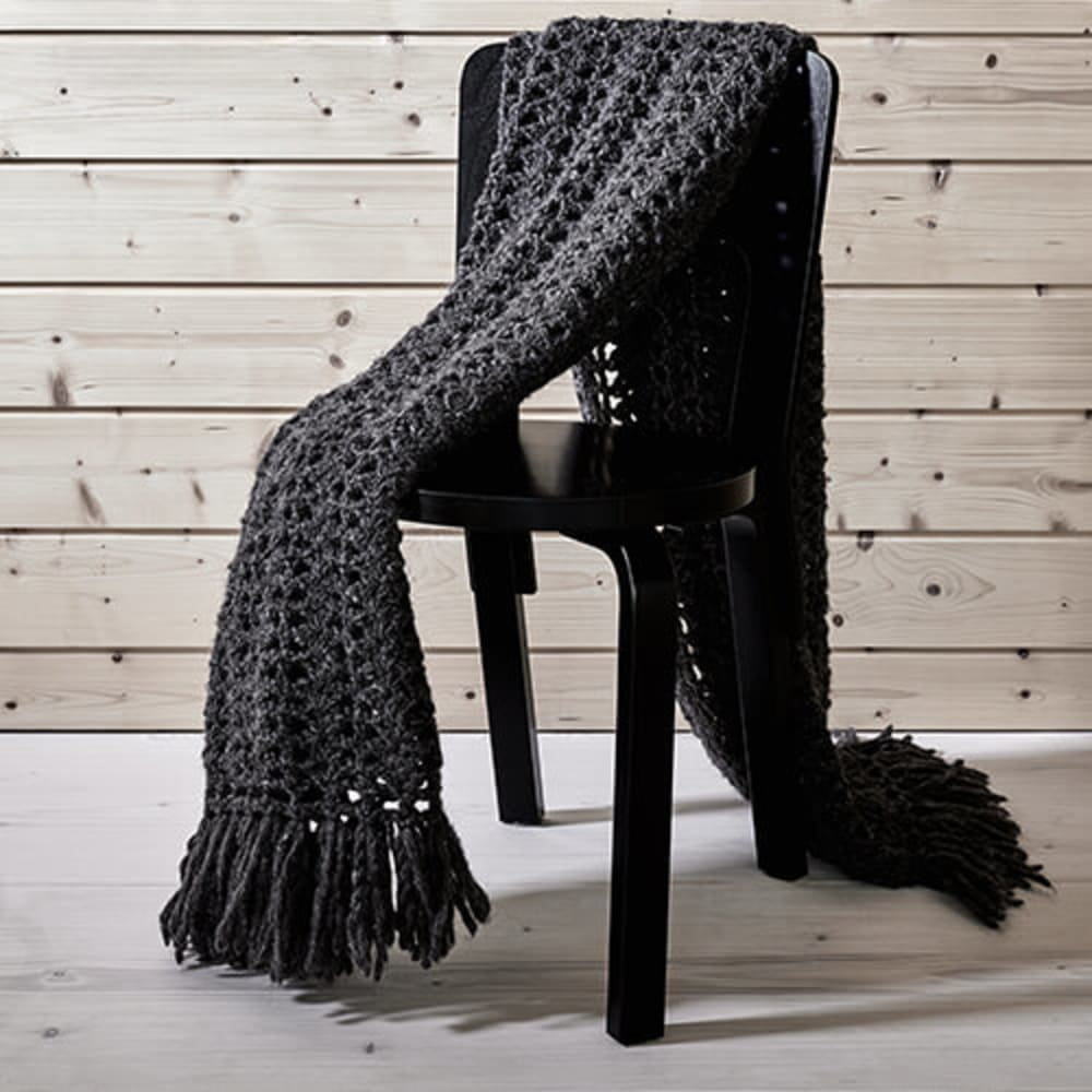 """Dark grey crocheted blanket lying on a chair.<span class=""""sr-only""""> (opened in a new window/tab)</span>"""
