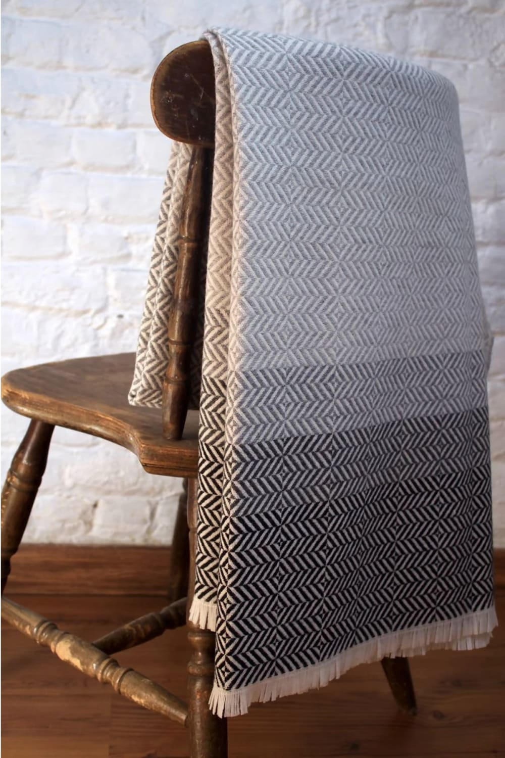 """Grey blanket laying on a vintage wood chair.<span class=""""sr-only""""> (opened in a new window/tab)</span>"""