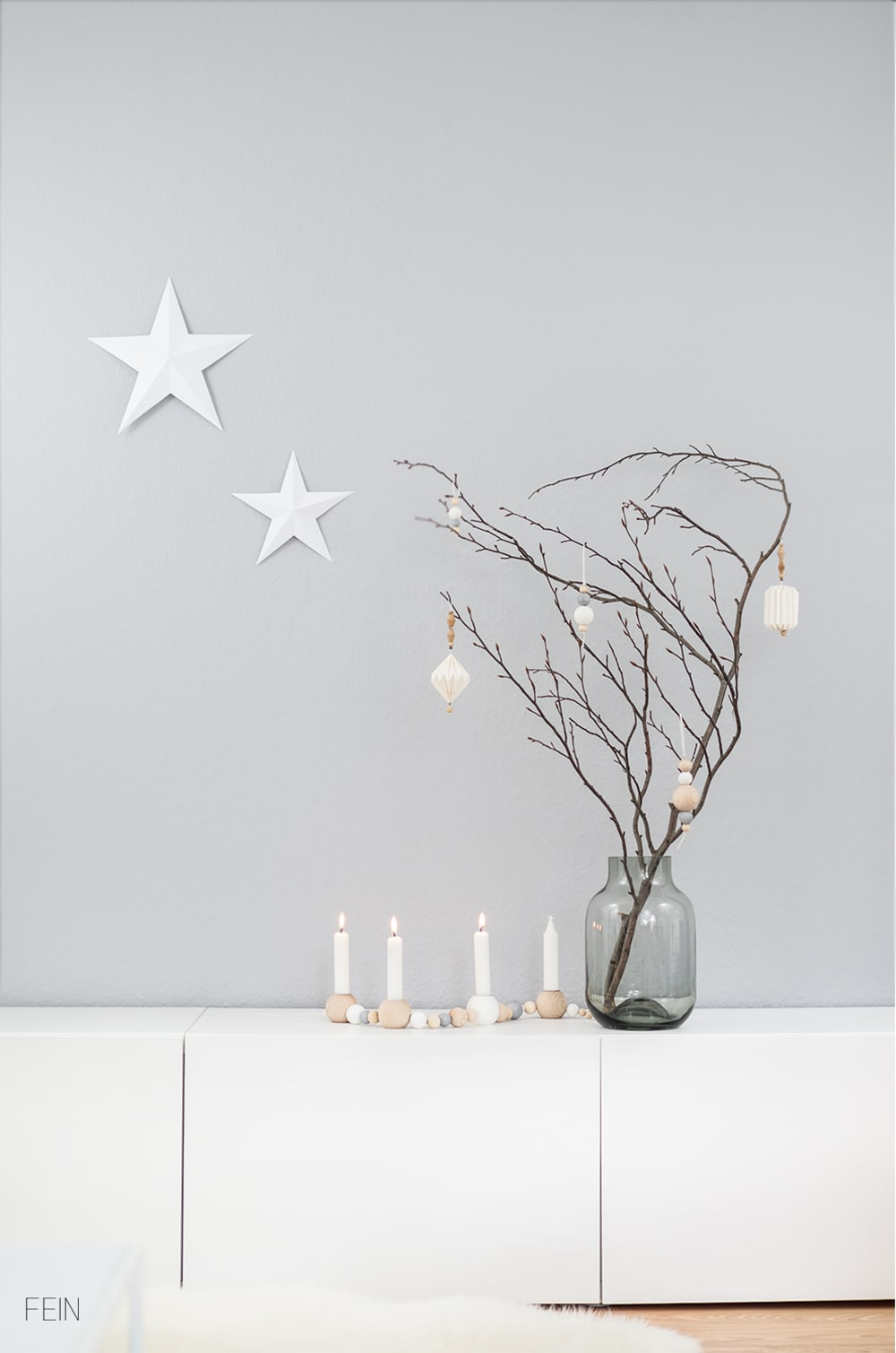 "Branch decorated with white ornaments on a light grey wall background.<span class=""sr-only""> (opened in a new window/tab)</span>"