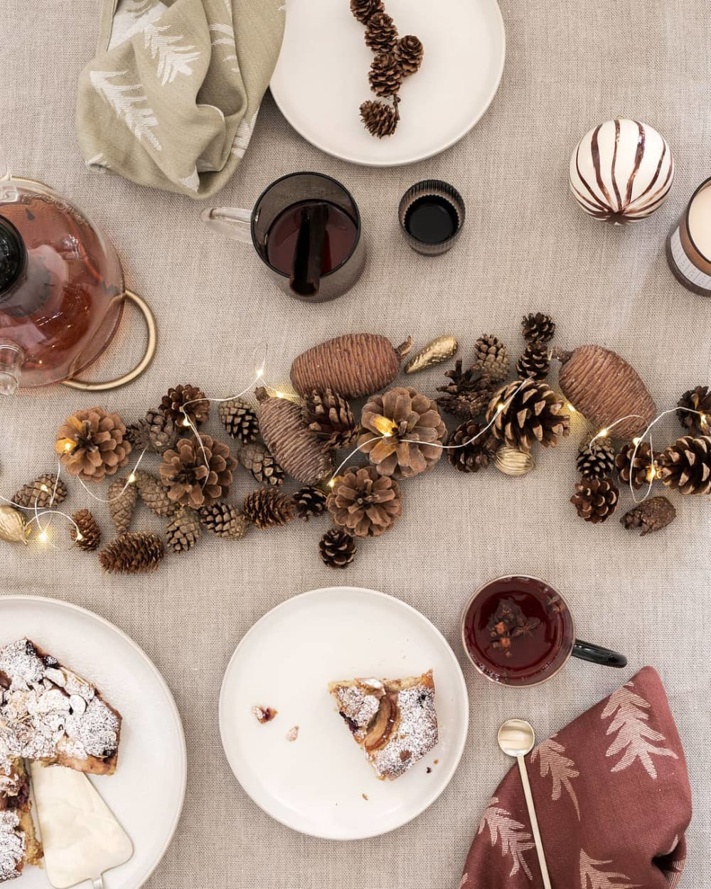"Top shot of a festive table setting with pinecones and string lights creating a sustainable Christmas centrepiece in the middle of the table.<span class=""sr-only""> (opened in a new window/tab)</span>"