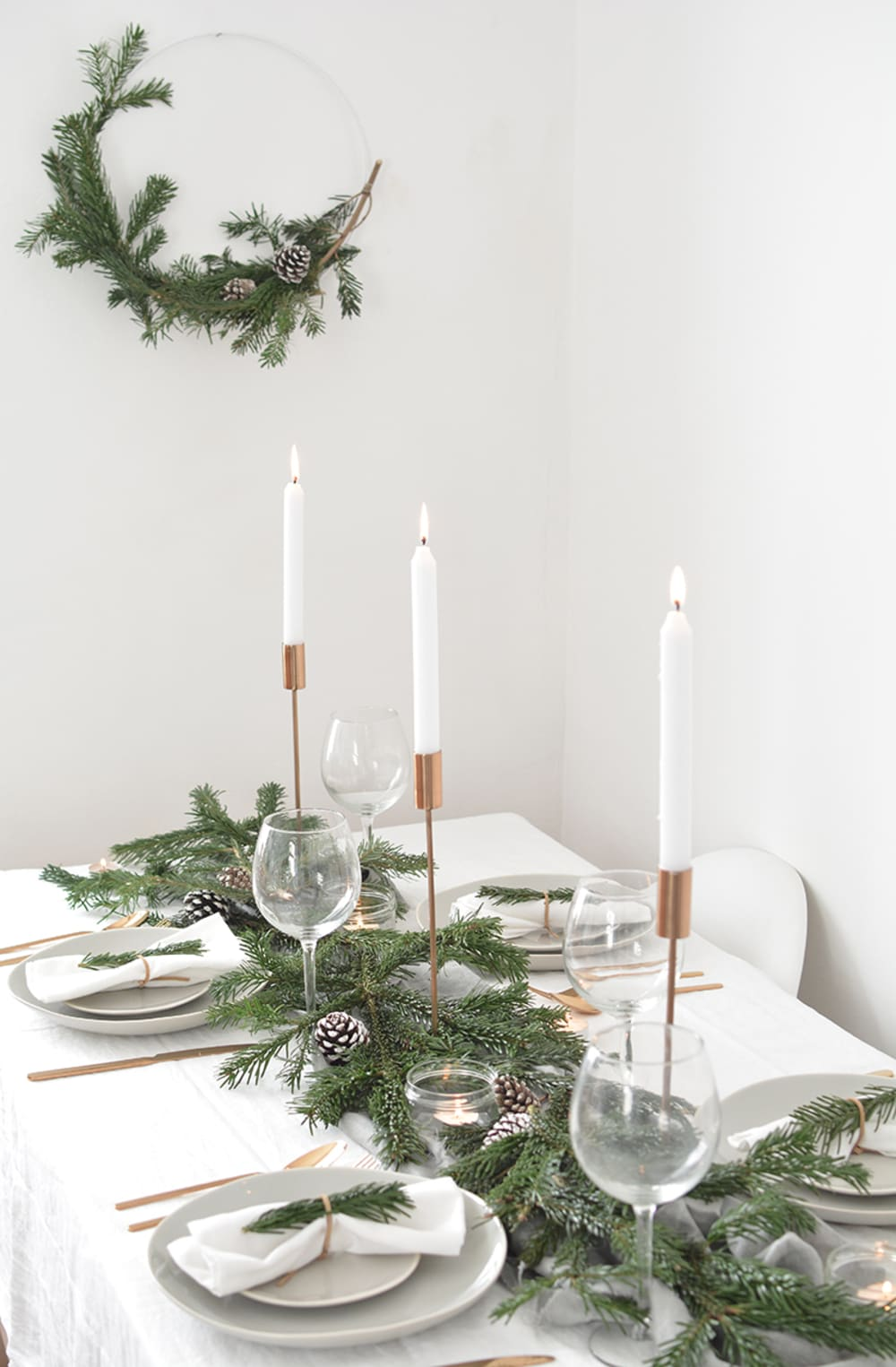 "Total white festive table setting with greens and tall candles as a centrepiece.<span class=""sr-only""> (opened in a new window/tab)</span>"