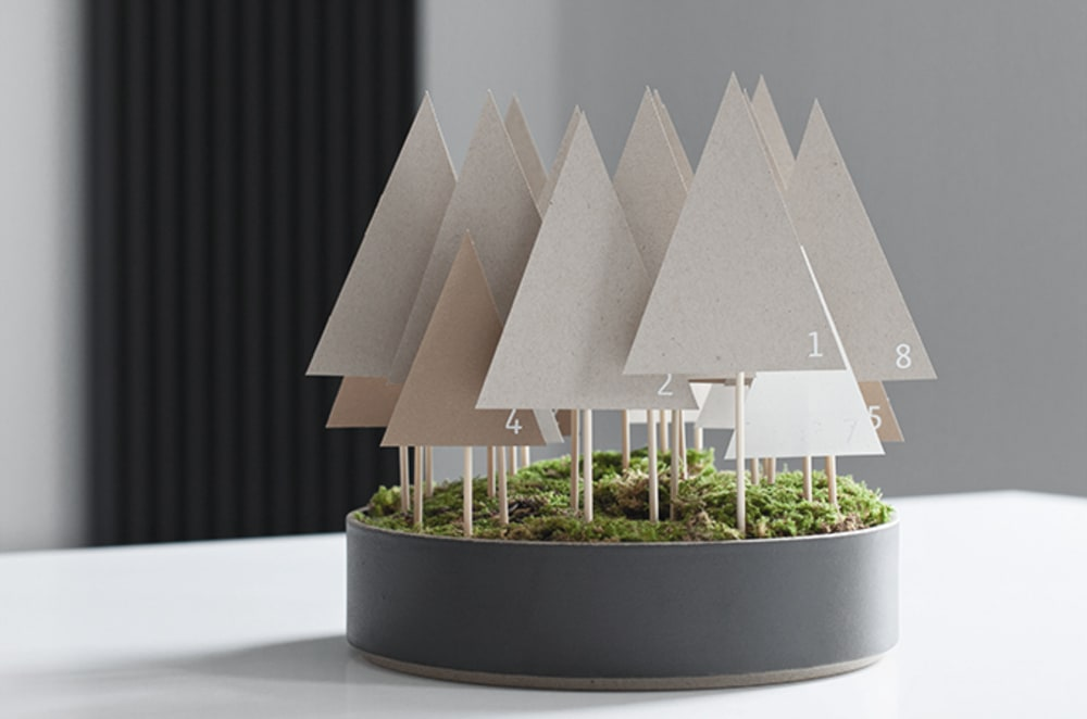"Advent calendar made of paper trees mounted on a wooden stick and tucked in a container onto a moss base.<span class=""sr-only""> (opened in a new window/tab)</span>"