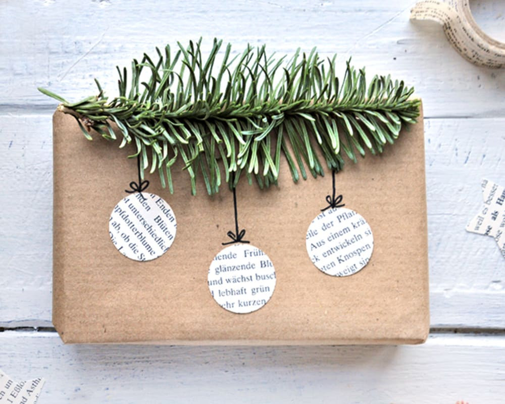 "Gift wrapped in brown paper and decorated with newspaper cut-outs in the shape of Christmas ornaments hanging from a fluffy twig of greenery.<span class=""sr-only""> (opened in a new window/tab)</span>"