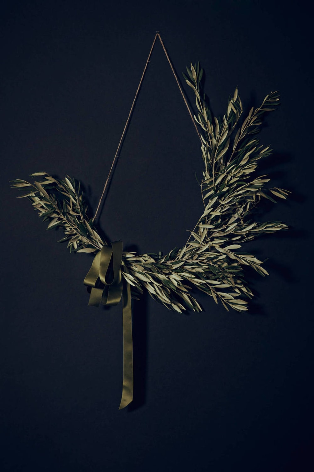 "Olive twigs asymmetric wreath on a dark blue background.<span class=""sr-only""> (opened in a new window/tab)</span>"