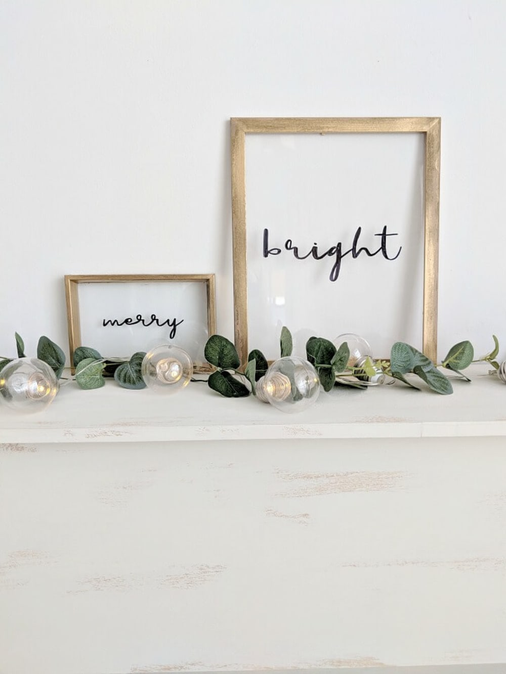 """Merry"" and ""Bright"" words written into the glass on a picture frame.<span class=""sr-only""> (opened in a new window/tab)</span>"