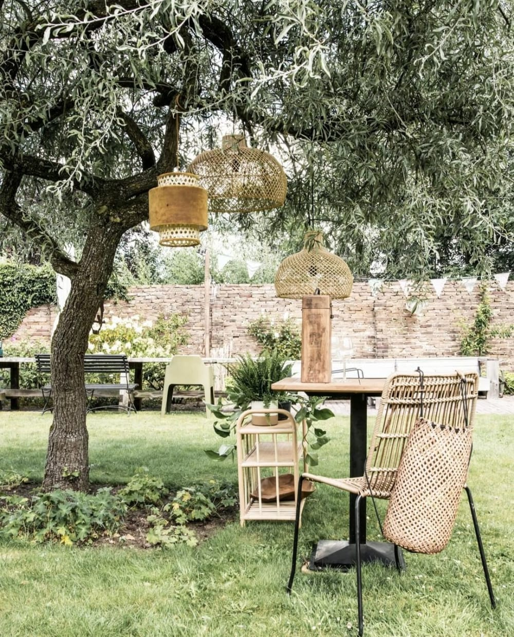"""Rattan pendant lamps and furniture styled in a garden under a big tree.<span class=""""sr-only""""> (opened in a new window/tab)</span>"""