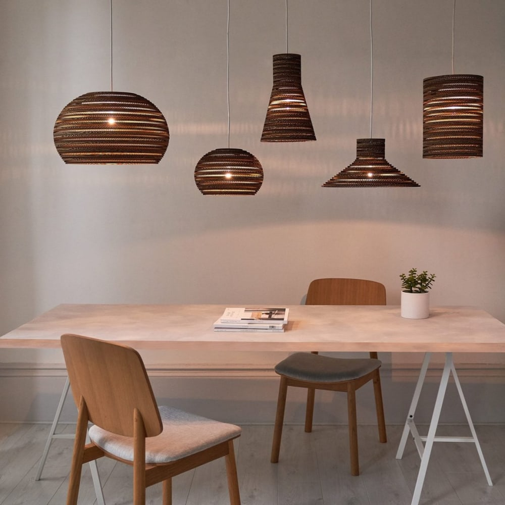 """Pendant lamps made of corrugated cardboard displayed over a table.<span class=""""sr-only""""> (opened in a new window/tab)</span>"""
