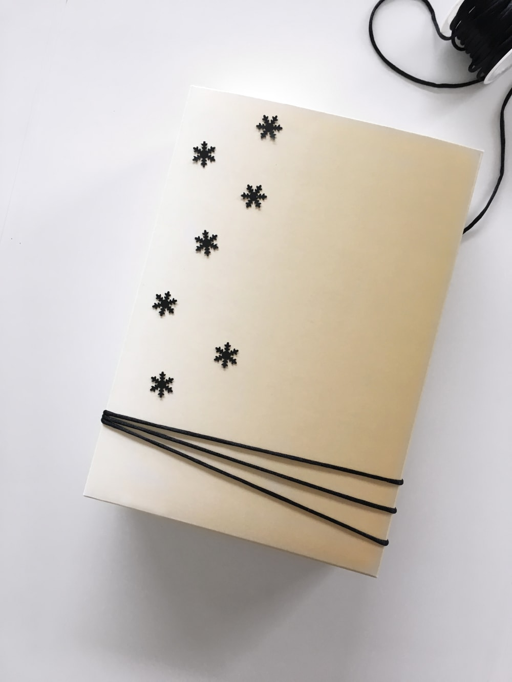 """Gift wrapped in a reused box decorated with paper snowflakes as an example of sustainable gift wrapping.<span class=""""sr-only""""> (opened in a new window/tab)</span>"""
