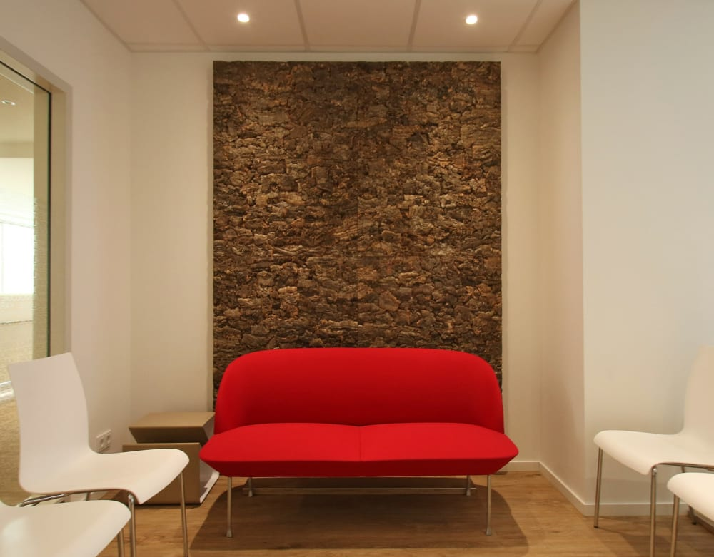 "Red two-seater sofa placed in front of a big framed cork bark panel.<span class=""sr-only""> (opened in a new window/tab)</span>"