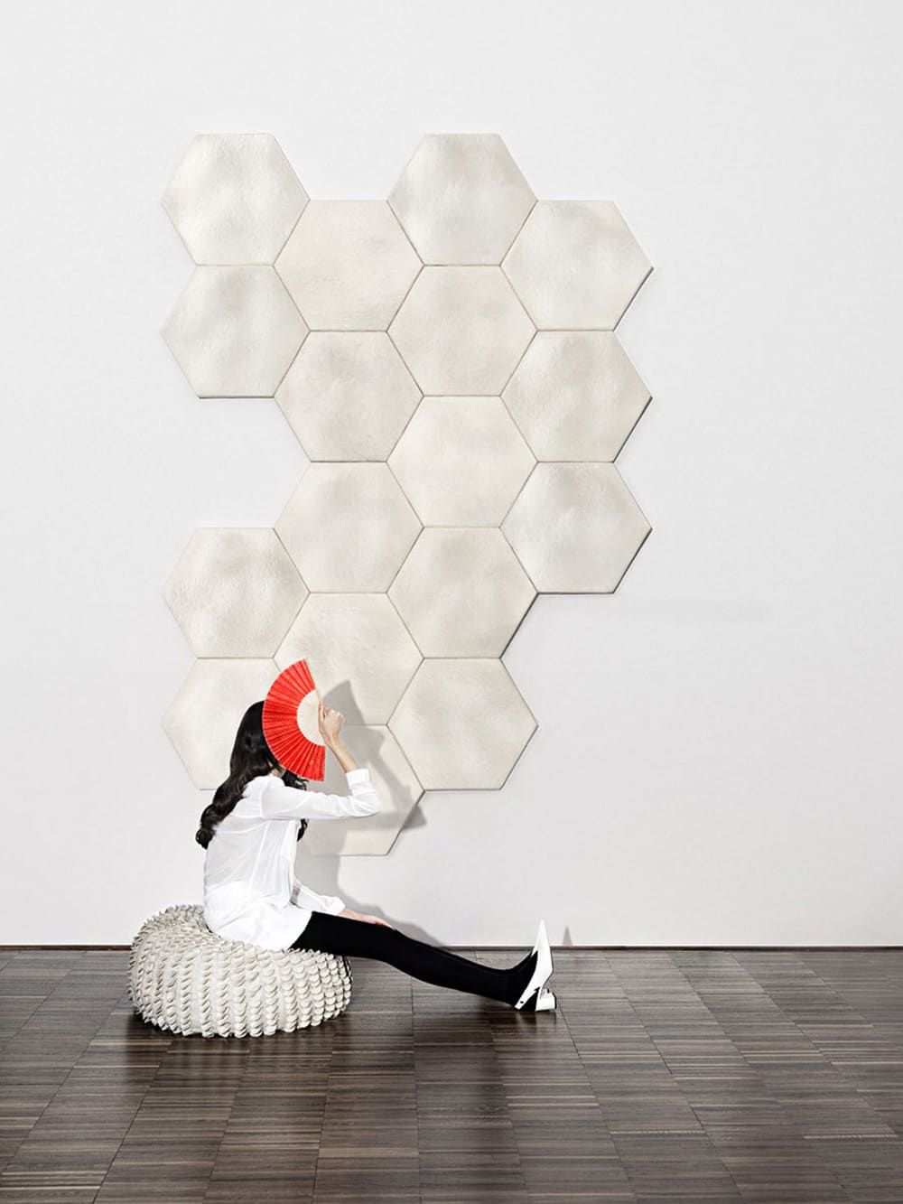 "Girl sitting in front of a wall decorated with acoustic tiles made of mushroom mycelium.<span class=""sr-only""> (opened in a new window/tab)</span>"
