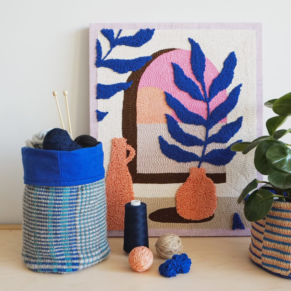 "Textile artwork leaning on a wall and styled with a plant.<span class=""sr-only""> (opened in a new window/tab)</span>"
