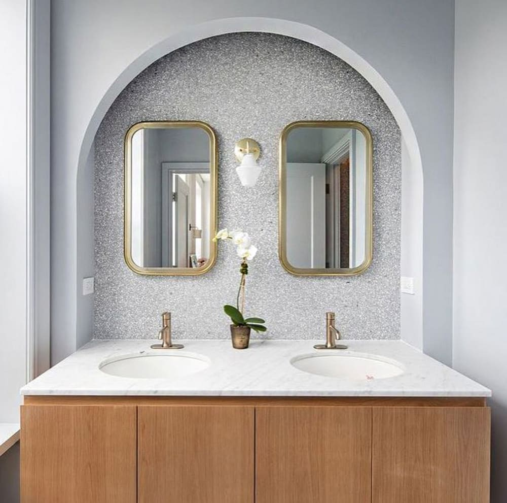 "Bathroom vanity with back wall covered with sustainable terrazzo tiles in grey.<span class=""sr-only""> (opened in a new window/tab)</span>"
