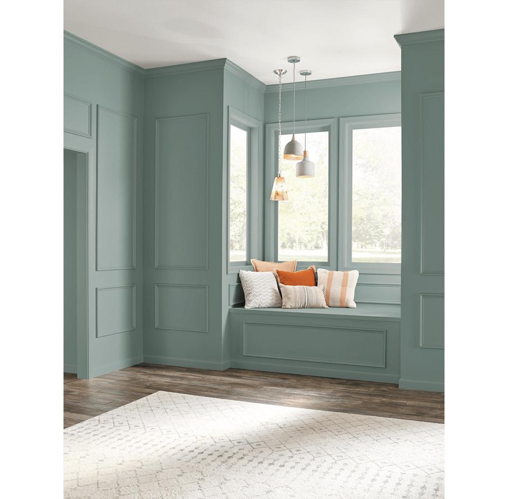 "Window seat in a classic home. The walls are painted with In the Moment (2018 colour of the year by Behr). To complete the seating area, white suspension lights and cushions in the tones of white and orange.<span class=""sr-only""> (opened in a new window/tab)</span>"