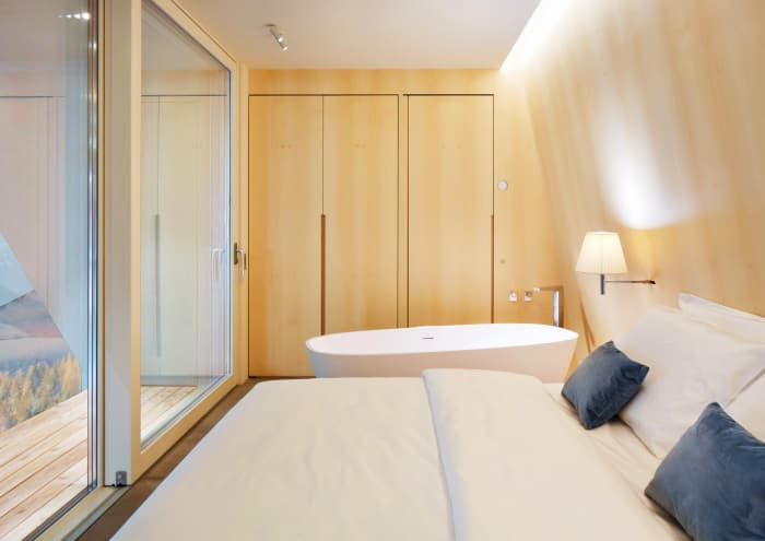 "The interior of EDEN luxury portable suite, an example of sustainable living and energy efficiency. View of bed, bathtub and hidden storage wall.<span class=""sr-only""> (opened in a new window/tab)</span>"