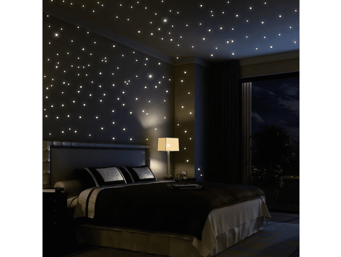 Tiny lights on the ceiling create a stunning starlight effect in this bedroom.