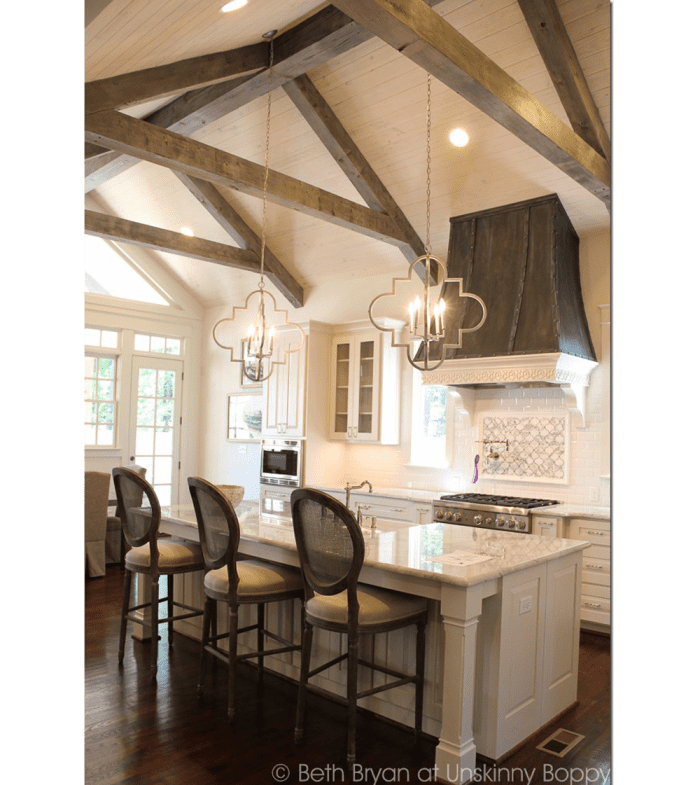 Kitchen with white ceiling and wooden truss vault.