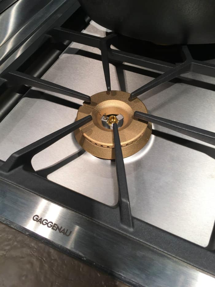Gold burner covers on a gas cooktop.