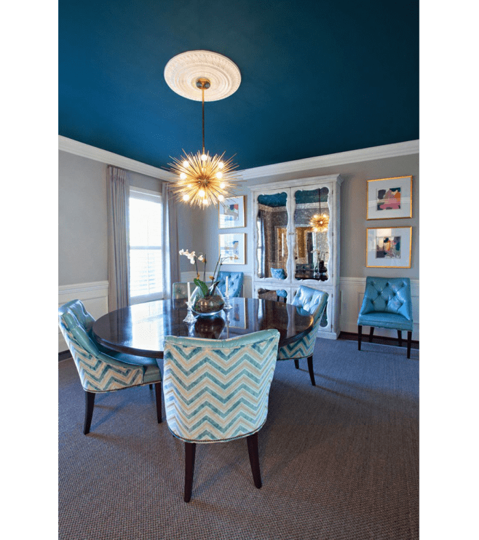 Dining room in the tones of turquoise. The bold blue ceiling is enriched with a contrasting white trim and a white rosette in the middle.