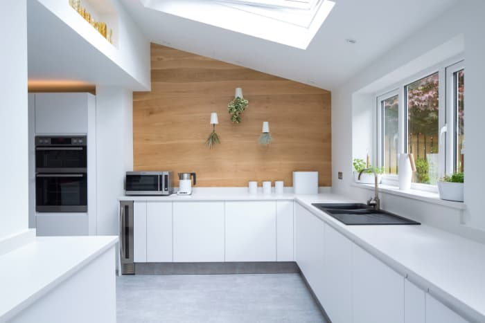 "Total white kitchen design with feature wall covered with Bolefloor curved boards.<span class=""sr-only""> (opened in a new window/tab)</span>"