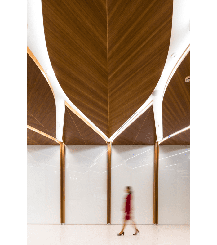 Corridor with big leaf-shaped wooden panels on the ceiling.