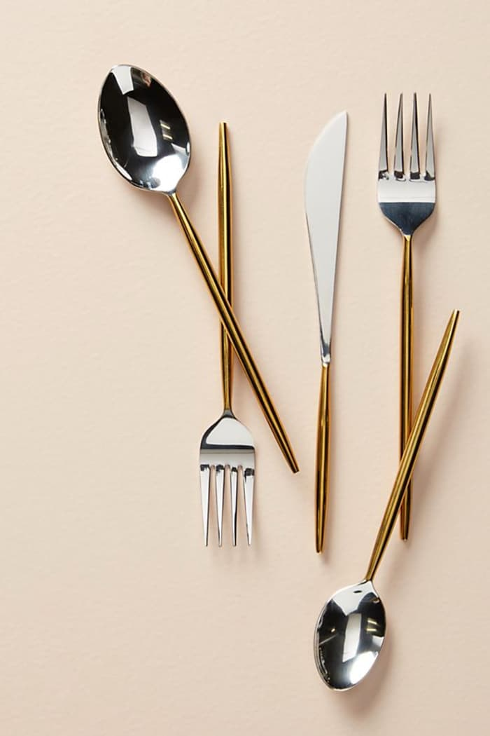 Minimalist cutlery set with shiny gold and silver colours; Gold by Anthropologie.